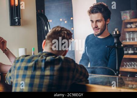 visitor is sharing secrets with a barmen. close up back view shot. man asking advice to a waiter. conversation, friendly chat - Stock Photo