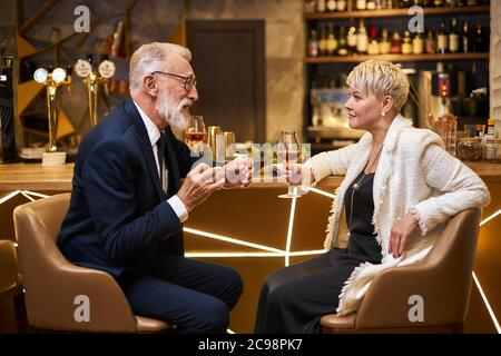Handsome man in beautiful tuxedo and woman in white blazer sit in expensive beautiful restaurant. Male declare his love. Romantic image, light view Stock Photo