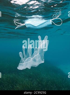Gloves underwater and face mask floating on water surface, plastic waste pollution in the sea, coronavirus COVID-19 pandemic, Mediterranean sea Stock Photo