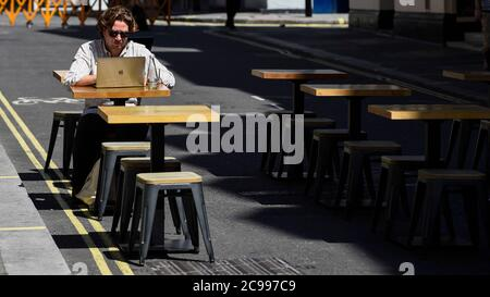 London, UK.  29 July 2020.  UK Weather:  A man works on his laptop in the sunshine on outdoor tables.  Some restaurants and cafes have set up tables and chairs outside during the ongoing coronavirus pandemic to practice social distancing.  Temperatures are forecast to exceed 30C by 31 July. Credit: Stephen Chung / Alamy Live News - Stock Photo