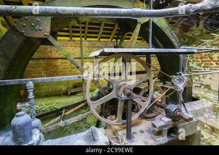 The waterwheel and vintage machinery in the restored Lower Pump House in Stourton, a small village near Stourhead, Wiltshire, south-west England