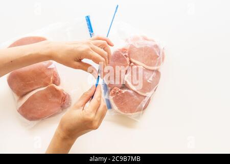 Raw boneless pork loin chops in zip lock bags. Woman packs meat in bags, close up view, white background, directly from above - Stock Photo