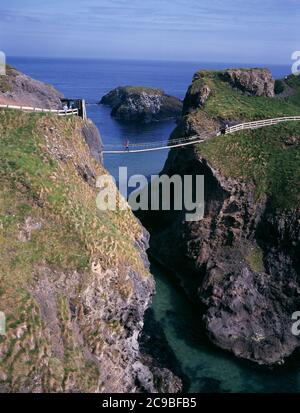 Carrick-A-Rede Rope Bridge with hikers crossing, near Ballintoy, County Antrim, Northern Ireland, United Kingdom - Stock Photo