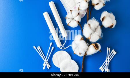All made of cotton. Hygiene accessories - sanitary napkins, cotton pads, cotton swabs, tampons on blue background. Concept of critical days - Stock Photo