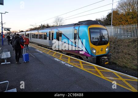 Passengers waiting to board a Siemens Class 185 Desiro Diesel Multiple Unit in Trans Pennine Express Livery at Thirsk Station, Yorkshire, UK - Stock Photo