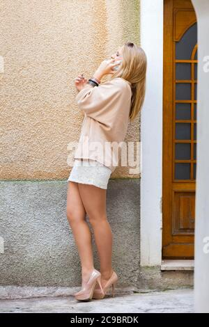 Legs heels blonde teengirl sheer tights talking chatting chat talk on smartphone phone device cellphone - Stock Photo