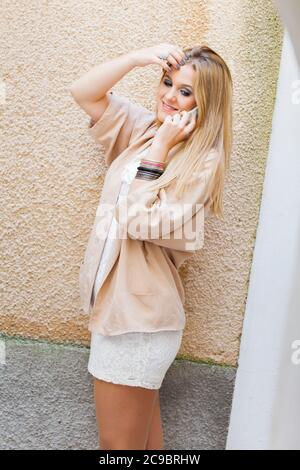 Blonde teengirl talking chatting chat talk on smartphone phone device cellphone slight smile optimistic - Stock Photo