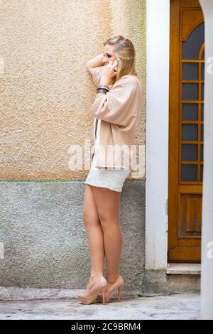 Legs heels blonde teengirl sheer tights talking chatting chat talk on smartphone phone device cellphone serious - Stock Photo