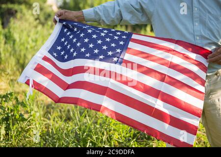 Patriotic senior man celebrates usa independence day on 4th of July with a national flag in his hands. Constitution and Citizenship Day. National Gran