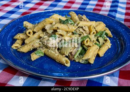 Cheesy Pesto, cream cheese, spinach and vegetarian chicken Penne pasta in a enamel plate on a picnic table at night, Camping dinner meal - Stock Photo