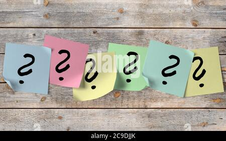 Wooden wall with sticky notes with question marks - Stock Photo