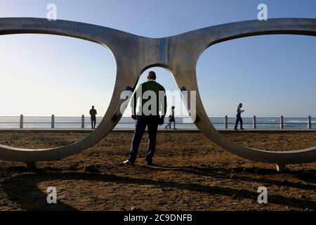 Everyday life on the promenade with Michael Elion's Madiba (Nelson Mandela) inspired public sculpture 'Perceiving Freedom' in Sea Point, Cape Town.