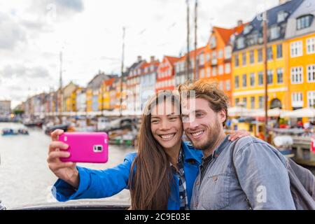 Copenhagen travel couple tourists taking selfie photo with phone camera. Smiling young people students at old port Nyhavn, tourism danish landmark in