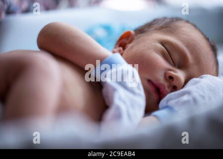 Shirtless newborn baby boy wearing white gloves sleeping - Stock Photo
