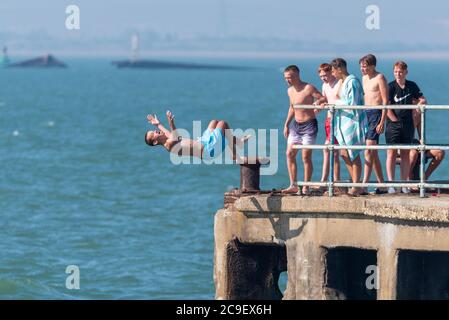 Southend on Sea, Essex, UK. 31st Jul, 2020. With the forecast high temperatures people are heading to the seafront to cool down, despite the COVID-19 Coronavirus advice. In the Thorpe Bay area to the east of Southend on Sea people are out enjoying the early morning high tide. Youngsters are jumping into the sea from the disused Barge Pier off Gunners Park - Stock Photo
