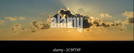Clouds with sun rays during sunset over the Wadden Sea on the north Dutch coast. - Stock Photo