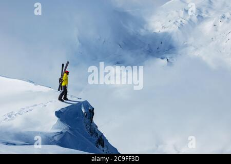 Adult man stand on the mountain top cliff with backpack and ski observe long alpine panorama to concur skiing - Stock Photo