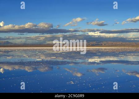 The Mirror Effect of Salar de Uyuni or Uyuni Salts Flats at the End of Rainy Season, UNESCO World Heritage Site in Bolivia, South America - Stock Photo