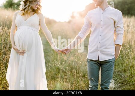 Young happy romantic pregnant couple walking in wild field in summer day. Pregnant woman in white dress and her handsome man expecting a baby
