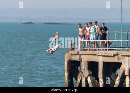 Youngsters jumping off Barge Pier in the Thames Estuary off Shoeburyness, Southend on Sea, Essex, UK. Tombstoning from old pier. Group of teenagers - Stock Photo