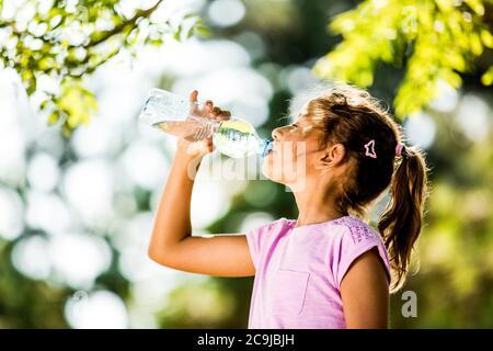 Girl drinking water from plastic bottle in park.