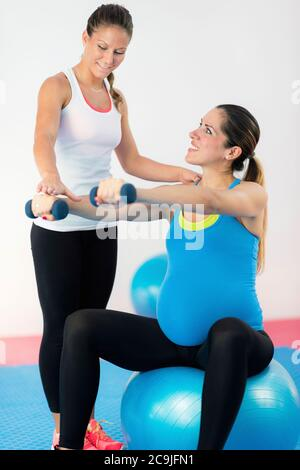 Healthy lifestyle in pregnancy. Pregnant woman maintaining healthy lifestyle, exercising with fitness instructor. - Stock Photo