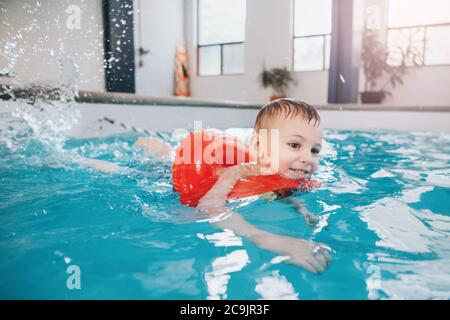 Cute Caucasian child boy in swimming pool with red float ring. Preschool boy training to swim in water indoor. Healthy active childhood lifestyle.
