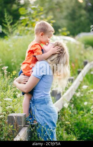 Young blonde Caucasian mother and boy toddler son hugging embracing kissing in park outdoor on summer day. Mom and child love and tenderness. Happy