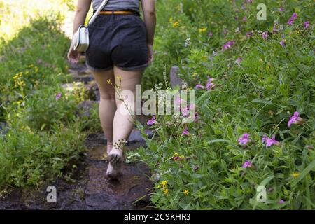A rear view of a young woman walking through Castle Crest Wildflower Garden in Crater Lake National Park in Oregon, USA.