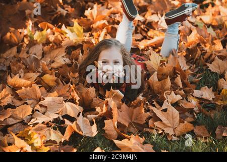 Cute little girl in autumn park. Little girl in leaves. Happy child laughing and playing leaves in autumn outdoors. Beautiful happy girl having fun in