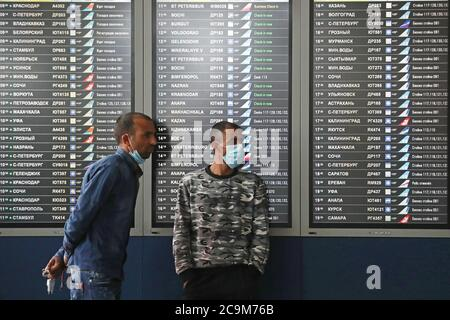 Moscow, Russia. 1st Aug, 2020. Men stand next to a flight information board at Vnukovo International Airport. Starting from 1 August, Russia partially resumes international flights, which were suspended in March due to the COVID-19 pandemic. The flights will be performed from Moscow, St Petersburg, and Rostov-on-Don to London, Ankara, Istanbul, and Zanzibar. On 1 August, the Aeroflot Airlines will operate two flights to London and three flights to Istanbul. Credit: Sergei Fadeichev/TASS/Alamy Live News - Stock Photo