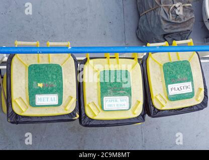 Three yellow wheelie bins for the segregation of garbage on the deck of a Vessel in the North Sea, seen from above. - Stock Photo