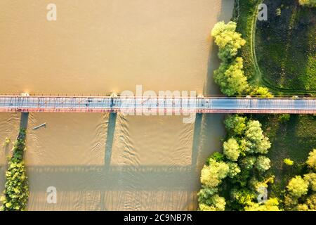 Aerial view of a narrow road bridge stretching over muddy wide river in green rural area. - Stock Photo