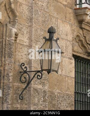 On a stone brick wall in old Havana is mounted this antique iron lantern - Stock Photo