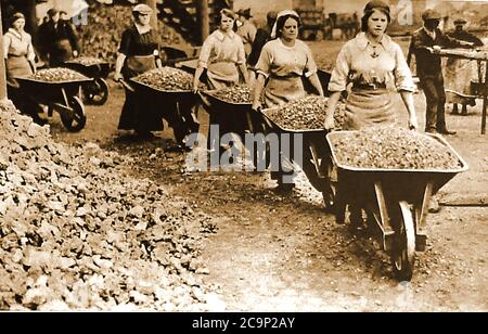 WWI - British Women working as building site labourers wheeling barrows of rubble. To help the war effort, thousands women were recruited into jobs vacated by men who had gone to fight in the war.