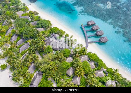Perfect aerial landscape, luxury tropical resort or hotel with water villas and beautiful beach scenery. Amazing bird eyes view in Maldives, landscape