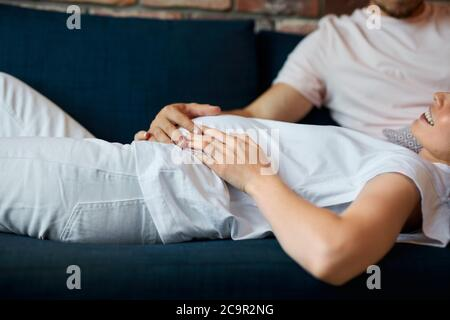 future father stroke woman's pregnant stomach, young caucasian man carefully look at belly, with love. at home