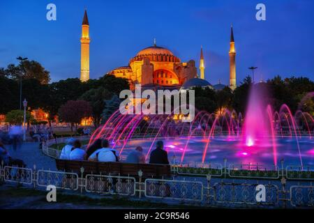 City of Istanbul in Turkey by night, people enjoy the view of Hagia Sophia (Ayasofya) and fountain in Sultanahmet Park - Stock Photo