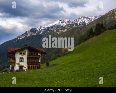 Lush green meadow,Idyllic spring mountain rural landscape. View over Stubaital or Stubai Valley near Innsbruck, Austria with rustic wooden cottage in - Stock Photo