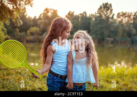 Little girls having fun outdoors after playing badminton. Sisters smiling with rackets in summer park. Kids walking.