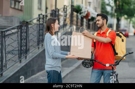 Shopping from home. Friendly courier with backpack and bicycle gives paper bag to client Stock Photo