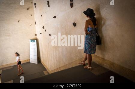 Woman in black hat and blue sun dress leaning against a wall and daughter on next landing in old building in Bologna Italy - Stock Photo