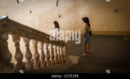 Mother and daughter standing on landing in old building with marble railing leading down to them in Bologna Italy - Stock Photo