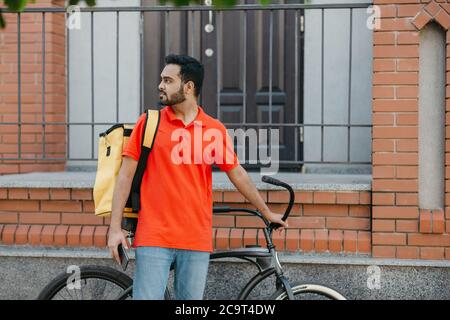 Work in city. Serious deliveryman with beard with backpack and bicycle, holding smartphone and looking for address Stock Photo