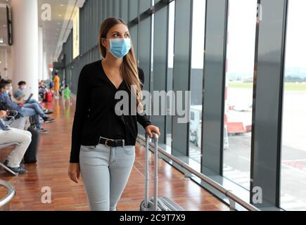 Young business woman with surgical mask and travel trolley luggage walking inside the airport. Female executive with suitcase on business trip during