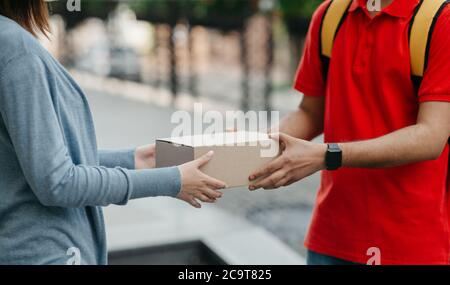 Online shopping and home delivery. Woman takes a box from courier with backpack Stock Photo