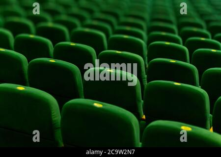 Green soft velvet chairs in the theater concert hall. Texture background for design.