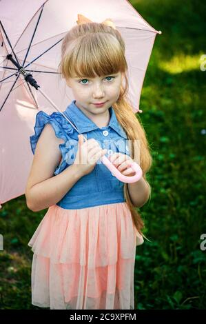 charming red-haired girl with a long braid and a pink umbrella is smiling. Girl with an umbrella in the garden - Stock Photo