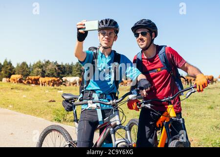 two young cyclists taking a selfie with the phone during their mountain bike route, concept of sport with friends and healthy lifestyle in nature, cop