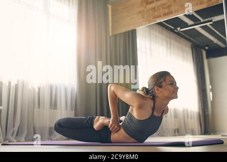 Smiling young woman practicing yoga in studio